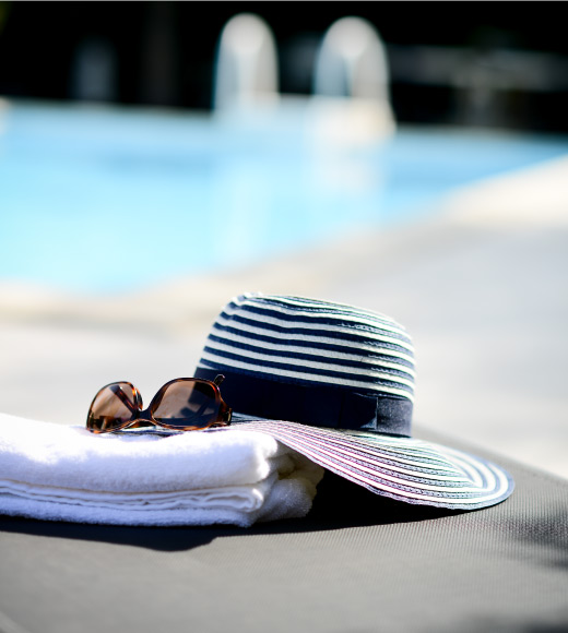hat, sunglasses and towel by the pool